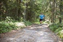 Vista frontale dell'uomo che fa jogging nella foresta — Foto stock