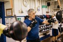 Тренировки для пожилых людей с боксерскими грушами, выборочная фокусировка — стоковое фото