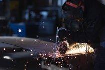 Junger Mann schneidet Metall in Werkstatt, differenzierter Fokus — Stockfoto