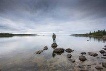 Людину, стоячи на скелі Бреш озера — стокове фото