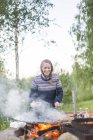 Woman cooking on fire pit, selective focus — Stock Photo