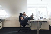 Geschäftsmann benutzt Desktop-Computer und schaut weg — Stockfoto