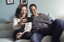 Young couple sitting on sofa, looking at smart phone and laughing — Stock Photo