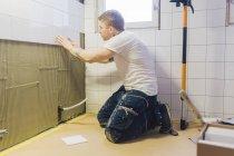 Tiler applicando piastrelle a parete in bagno — Foto stock