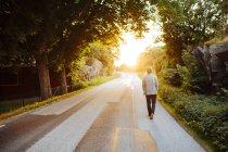 Вид сзади на человека, идущего по дороге на закате — стоковое фото
