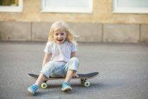 Дівчинка сидить на скейтборд, зосередити увагу на передньому плані — стокове фото