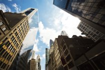 Вгору зору хмарочосів проти неба в Манхеттен, Нью-Йорк — стокове фото