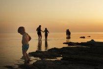 Menino com família na praia ao entardecer, foco seletivo — Fotografia de Stock