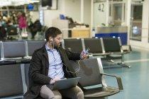 Uomo che usando computer portatile e smartphone in sala d'attesa aeroporto — Foto stock