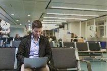Man using laptop at airport waiting area — Stock Photo