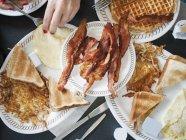 Vue recadrée de femme mangeant le petit déjeuner avec le bacon, les pains grillés et les gaufres — Photo de stock
