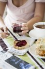 Cropped view of woman spreading jam on toast, selective focus — стоковое фото