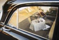 Picnic basket on car back seat — Stock Photo