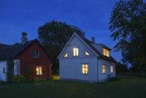 Beleuchtete Häuser in der Abenddämmerung, Nordeuropa — Stockfoto