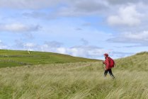 Side view of senior woman hiking in grassland — Stock Photo