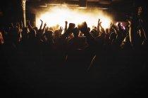 Siluetas de personas bailando en concierto, enfoque selectivo - foto de stock