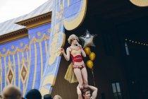 Female acrobat balancing on male acrobat on stage — Stock Photo