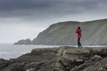 Senior woman standing on rock and looking at view — Stock Photo