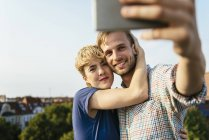 Young couple hugging and taking selfie with smartphone on town rooftop — Stock Photo