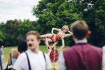 Acróbatas de circo jóvenes actuando en el parque - foto de stock