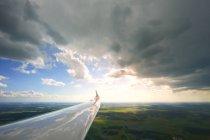 Ala de avión con nubes reflejo sobre el paisaje verde - foto de stock