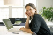 Portrait of young woman using laptop and smiling at camera — Stock Photo
