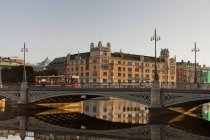 Bridge with moving bus and buildings in Stockholm old town reflecting in water — Stock Photo
