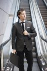 Young businessman with briefcase standing by escalator — Stock Photo
