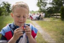 Junge isst Erdbeere, Fokus auf Vordergrund — Stockfoto