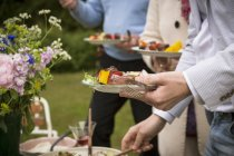 People eating food during midsummer celebrations — Stock Photo