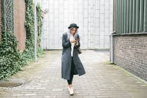 Young woman in long overcoat and bowler hat using smartphone on street — Stock Photo
