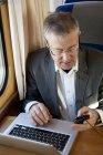 Vista de ángulo alto de los mensajes de texto de hombre de negocios en tren - foto de stock