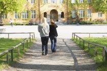 Vista traseira das mulheres jovens, caminhando em direção a construção de escola — Fotografia de Stock