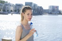 Woman standing with bottle of water in hands — Stock Photo