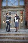 Дві жінки, що стоїть перед входом до будинку і говорити — стокове фото