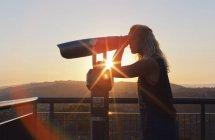 Mulher usando binóculos de moedas ao pôr do sol em Los Angeles — Fotografia de Stock