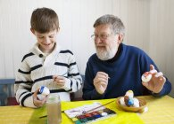 Дедушка с внуком украшает пасхальные яйца — стоковое фото