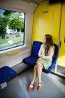 Девочка-подросток смотрит через окно на поезд — стоковое фото