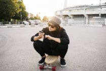 Skateboarder texting with smartphone at sunset on parking lot — Stock Photo