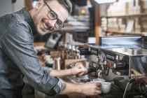 Улыбающийся бариста варит кофе и смотрит в камеру — стоковое фото