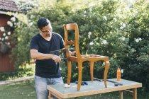 Mid adult man repairing chair outdoors in Kvarnstugan, Sweden — Stock Photo