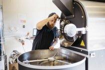 Homme utilisant une machine de torréfaction de café, mise au point sélective — Photo de stock