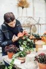 Молодая женщина выращивает растения в питомнике — стоковое фото