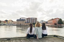 Tre giovani donne sedute sul molo di Karlskrona, Svezia — Foto stock