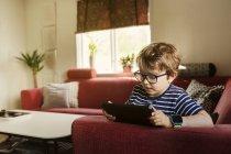 Мальчик играет на цифровом планшете в гостиной, сосредоточиться на переднем плане — стоковое фото