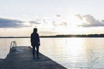 Середній дорослий жінка стоячи на пірсі, фокус на передньому плані — стокове фото
