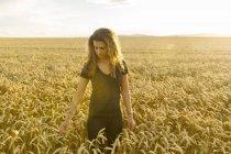 Девочка-подросток смотрит вниз на пшеничное поле, фокусируется на переднем плане — стоковое фото