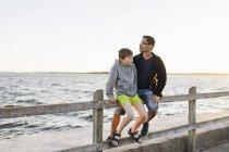 Padre e figlio seduti sul molo al tramonto a Blekinge, Svezia — Foto stock