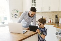 Mid adult man and boy looking at tablet in domestic kitchen — Stock Photo