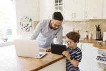 Hombre adulto medio y niño mirando tableta en la cocina doméstica - foto de stock